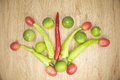 Fresh red and green goat pepper lemon and tomato with place on wood background Stock Photo