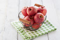 Fresh red juicy apples in a basket on a green textile on a wooden background