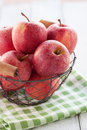Fresh red juicy apples in a basket on a green textile on a wooden background Royalty Free Stock Photo