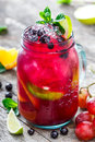 Fresh red lemonade with mint, black currant, lime, orange, grapes and ice in glass jar on wooden background Royalty Free Stock Photo