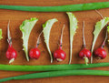 Fresh red radish and salad leaves on a wooden surface lie Royalty Free Stock Image