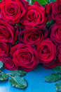 Fresh red roses on blue table wooden Stock Photography