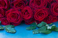 Fresh red roses on table row blue wooden Stock Photo