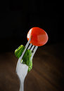 Fresh red tomato and salad on a fork dark background Stock Photo