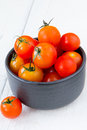Fresh red tomatoes in black bowl on white wooden table Royalty Free Stock Photo