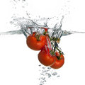 Fresh red tomatoes splash in water isolated on white background closeup of and health falling into clear with big Stock Photos