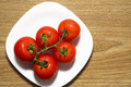 Fresh red tomatoes in white plate on wooden table Royalty Free Stock Photo