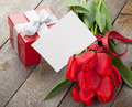 Fresh red tulips with gift box and greeting card