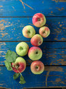 Fresh and ripe apple on blue table wooden top view Stock Image