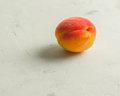 Fresh and ripe apricots on a white stone background. Royalty Free Stock Photo