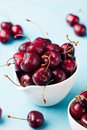 Fresh ripe black cherries in a white bowl on a blue stone background Royalty Free Stock Photo