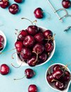 Fresh ripe black cherries in a white bowl on a blue stone background. Top view. Royalty Free Stock Photo