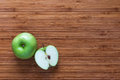 Fresh ripe green apple Granny Smith: whole and sliced in half on a wooden cutting board. Nature fruit concept. Royalty Free Stock Photo