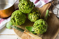 Fresh ripe green artichokes on cutting board, knife, copper dipper in the background Royalty Free Stock Photo