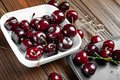 Fresh ripe juicy sweet cherries in white and black plates on a wooden background. Wet sweet cherry with water droplets Royalty Free Stock Photo