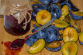 Fresh ripe plum - raw materials for making homemade jam and a glass jar with jam Royalty Free Stock Photo