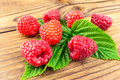 Fresh, ripe raspberries on leaves, rustic wooden background. Royalty Free Stock Photo