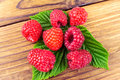 Fresh, ripe raspberries on leaves, rustic wooden background Royalty Free Stock Photo