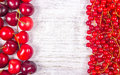 Fresh ripe red currants and cherries on rustic wood background. Royalty Free Stock Photo
