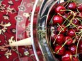 Sweet ripe cherries in a metal plate on a glass table.