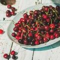 Fresh ripe sweet cherries in plate on rustic garden table
