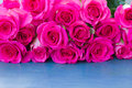Fresh roses on table pink row blue wooden Stock Photos
