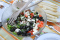Fresh salad with black olives goat cheese tomatoes green peppers and herbs in front of a bowl of white asparagus Royalty Free Stock Images