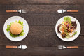 Fresh salad and burger on the wooden background contrasting foo food Royalty Free Stock Photos