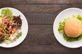 Fresh salad and burger on the wooden background contrasting foo food Royalty Free Stock Photo