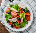 Fresh salad with chicken breast, arugula, black olives,red pepper, lettuce, fresh sald leaves and tomato on a white plate on woode Royalty Free Stock Photo