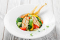 Fresh salad with chicken breast, baby spinach, basil, cherry tomatoes, pear, cucumber on plate on wooden background Royalty Free Stock Photo