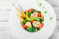 Fresh salad with chicken breast, baby spinach, basil, cherry tomatoes, pear, cucumber on plate on wooden background close up. Royalty Free Stock Photo