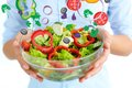 Fresh salad close up of vegetable in bowl held by female Royalty Free Stock Images