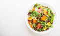 Fresh salad with fruits and greens on white wooden background top view with space for text