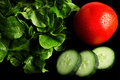 Fresh salad ingredients on black background healthy and in vivid colors Royalty Free Stock Photos