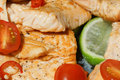 Fresh salmon with lemon closeup of freshly cooked black pepper tomatoes and hot chili Royalty Free Stock Image