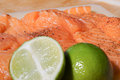 Fresh salmon steaks uncooked peppered and with limes placed on top Stock Photos