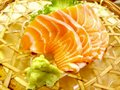 stock image of  Fresh sashimi salmon with wasabi and lettuce served in a woven rattan dish