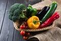 Fresh seasonal vegetables in basket on rustic wooden table
