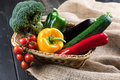 Fresh seasonal vegetables in basket on sackcloth