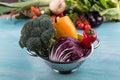 Fresh seasonal vegetables in colander on wooden table background