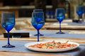 Fresh served pizza on restaurant table empty blue glasses and Stock Photography