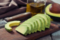 Fresh sliced avocado on cutting board over wooden background Stock Photos