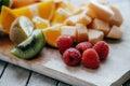 Fresh sliced fruit: raspberry, kiwi, melon, oranges on a wooden Royalty Free Stock Photo