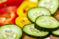 Fresh sliced vegetables on a wooden board closeup of pepper and cucumber Royalty Free Stock Image