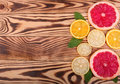 Fresh slices of juicy orange, ripe lemon, and organic grapefruit with leaves of mint on a wooden background, top view.