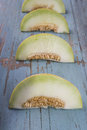 Fresh slices of yellow melon or cantaloupe on old wooden grungy Royalty Free Stock Photo