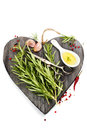 Fresh spices on heart shaped cutting board herbs and over white health or vehetarian concept Stock Photos