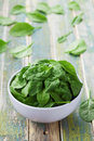Fresh spinach leaves in bowl on rustic kitchen table Royalty Free Stock Photo