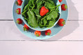 Fresh spinach salad with spinach and strawberries on wooden light pink table Royalty Free Stock Photo